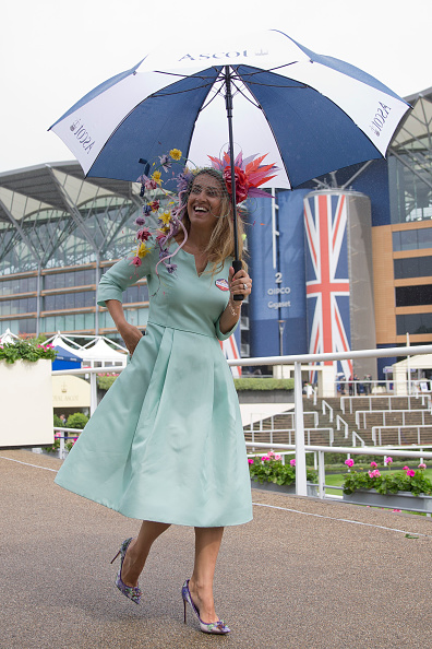 A racegoer shelters from the rain during a downpour on the first day on the first day of the Royal Ascot horse racing meet, in Ascot, west of London, on June 14, 2016.  / AFP / JUSTIN TALLIS        (Photo credit should read JUSTIN TALLIS/AFP/Getty Images) Nazer wears the Suzannah 'Burlington' dress with Edwina Ibbotson millinery
